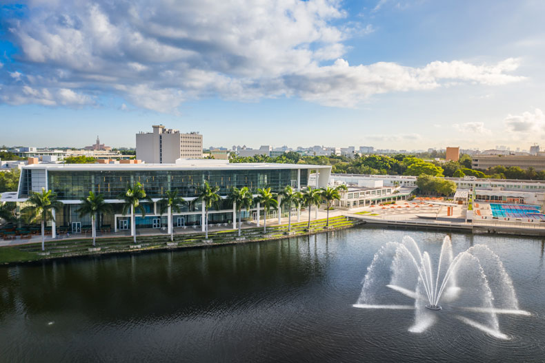 An aerial view of the Shalala Student Center on Lake Osceola and Cobb Fountain, with the City of Coral Gables in the distance.